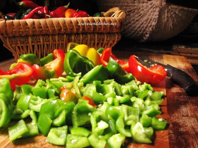 Bell peppers cut into 1 inch pieces with basket in background