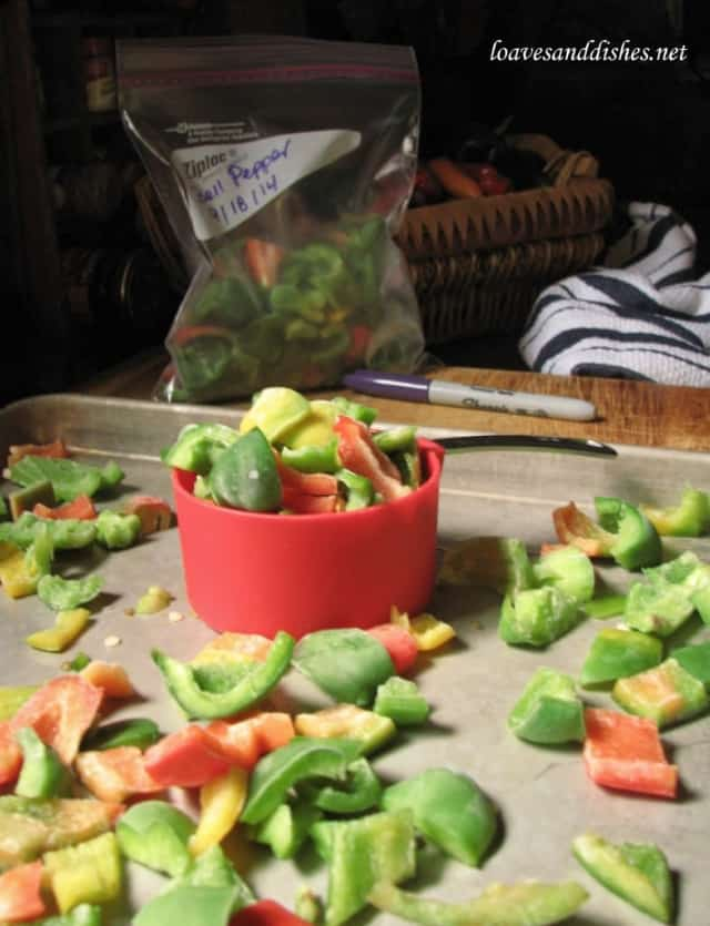 1/2 cup measure holding frozen bell pepper pieces