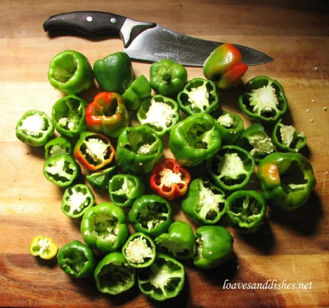 cutting board with peppers cut in half with knife