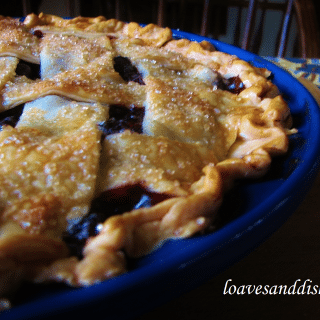 blueberry pie close up in blue pie dish on cutting board