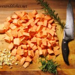 cut up sweet potatos with sprig of rosemary and garlic on cutting board