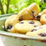 several mini blueberry muffins in a green bowl on a white table cloth