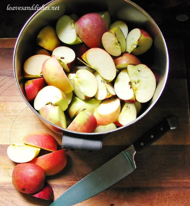 Apples in a large sauce pot with knife on cutting board