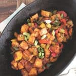 a black cast iron oval pan with sweet potato hash inside with wood in back ground