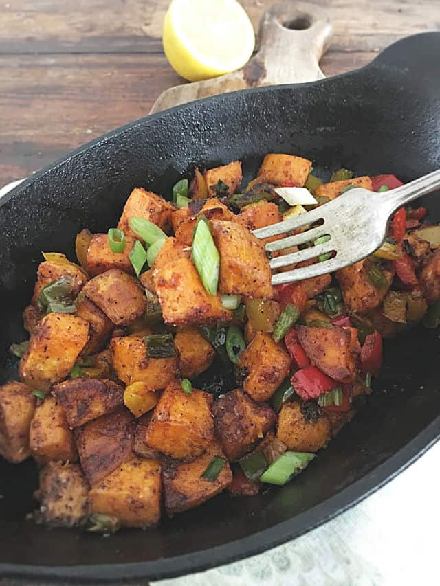 A fork picking up a piece of the sweet potato hash from an oval cast iron pan with wood in the background