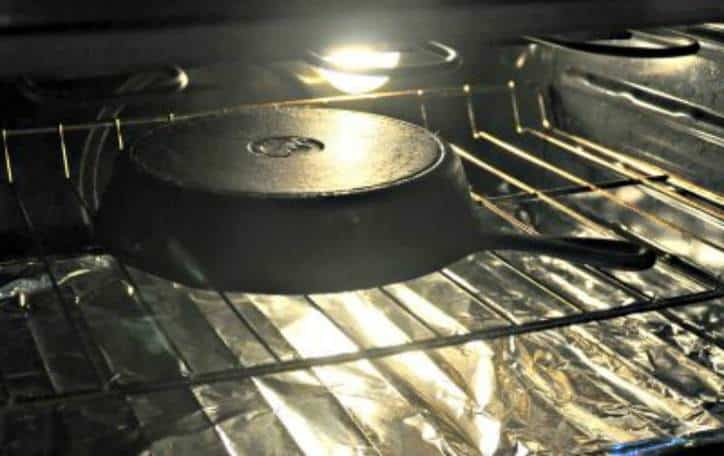 A photo of the pan in the oven for how to season a cast iron skillet