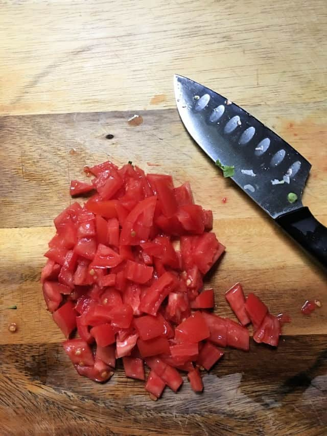 tomato diced with knife on cutting board