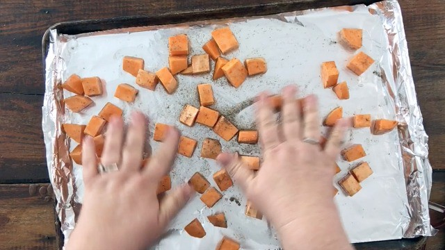 Hands spreading cubed sweet potatoes out on an oiled half sheet pan covered with foil