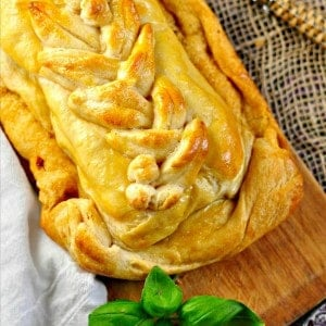 Braided pastry on a cutting board with fresh basil