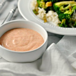 A photo of a bowl of Yum Yum Sauce beside a plate of broccoli and rice for Yum yum sauce