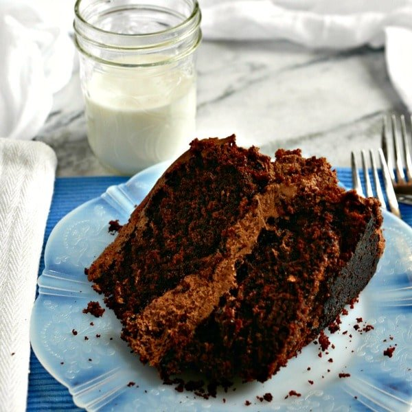 a close up photo of homemade chocolate cake on a white plate with crumbs, two forks and a half pint jar of milk