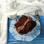 The Chocolate Cake on a plate with two forks and a blue place mat