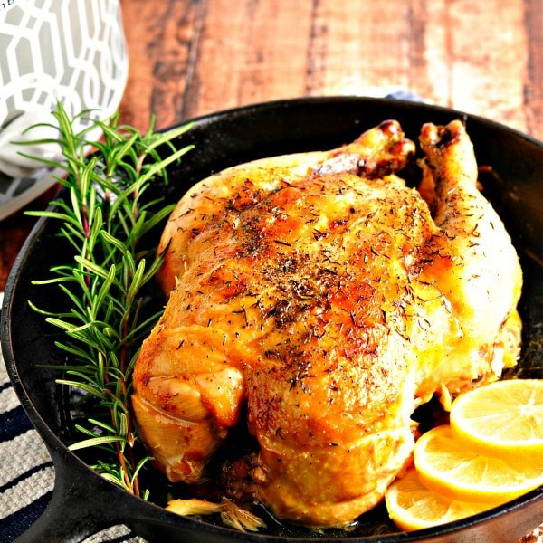 roasted chicken in a cast iron pan with fresh rosemary and lemon slices