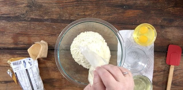 A photo of pouring cake mix into a clear bowl