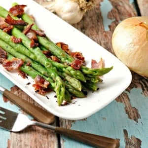 Asparagus on a white plate with bacon sprinkled on top