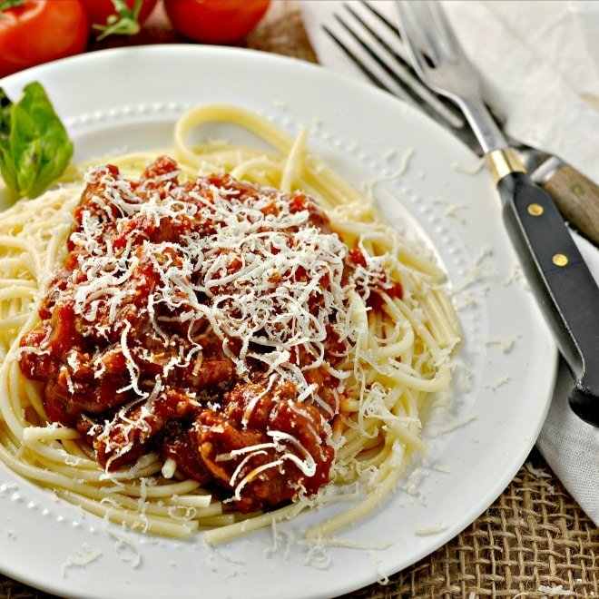 Spaghetti with red mead sauce on a white plate with two forks