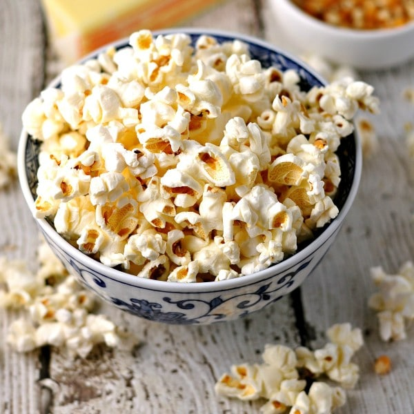 A blue and white bowl with homemade popcorn in and around it