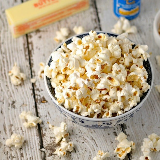 popcorn in bowl with butter and salt in the back ground