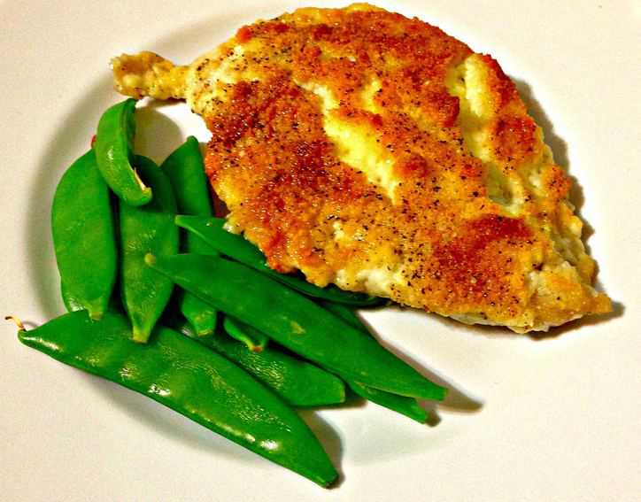 Chicken with breading and green snow peas on a white plate