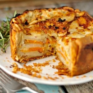 Root Vegetable Rosemary Gratin with a slice removed on a white plate