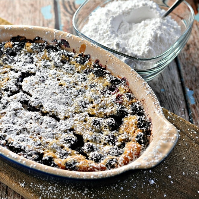 Rustic Blueberry Cake Clafoutis in a baking dish with powdered sugar sprinkled on top