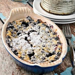 Rustic Blueberry Cake Clafoutis on a wooden table with a fork and powdered sugar