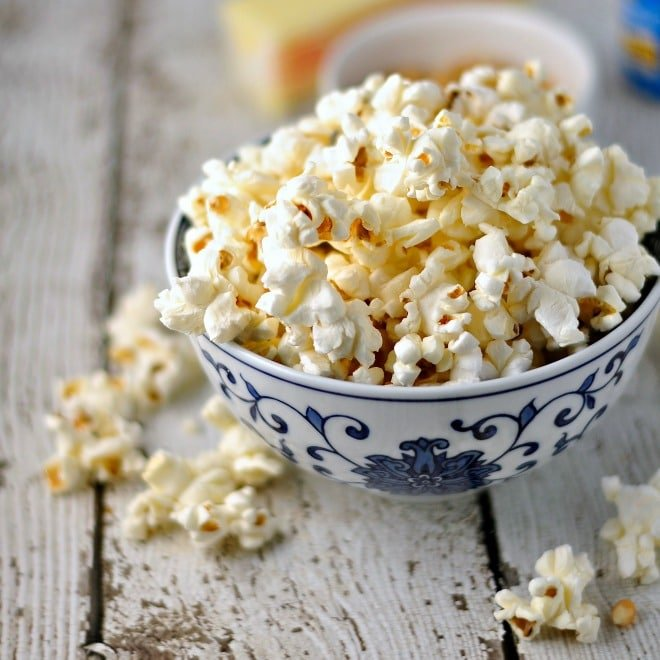 Blue flowered bowl holding too much popcorn with some spilling over onto the white wooden counter