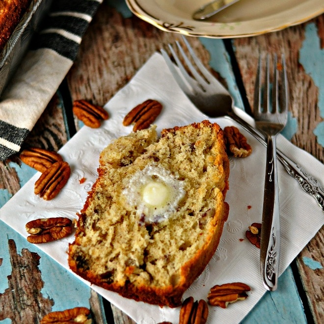 slice of banana bread with pecans, forks and a plate. napkin in background