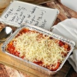 Easy Gift Lasagna in an aluminum tin on a cutting board with a spoon and a white napkin