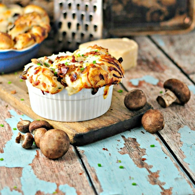 Mushroom (Bacon) Pull Apart Bread in a white dish with button mushrooms sprinkled around
