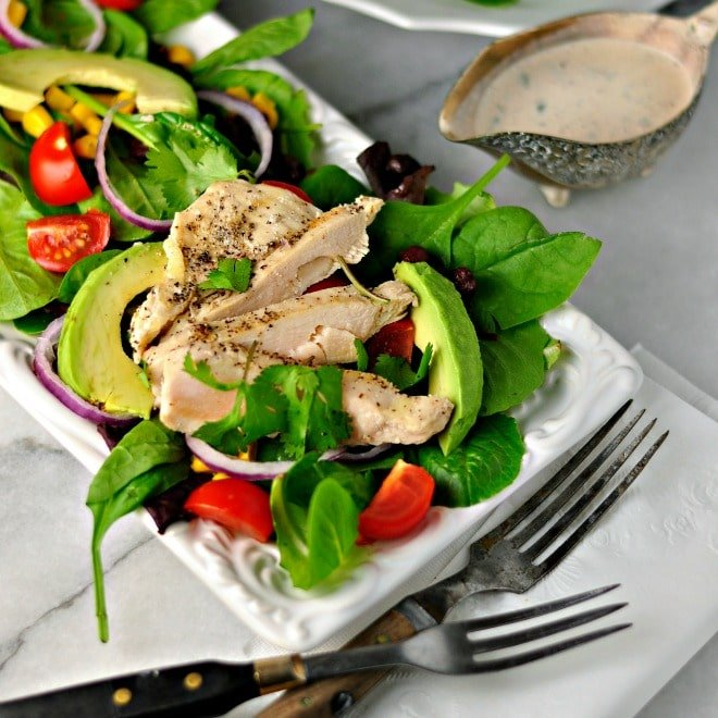 southwest chiptole chicken salad with chicken and avocados on a white plate with two forks and a small bowl of dressing