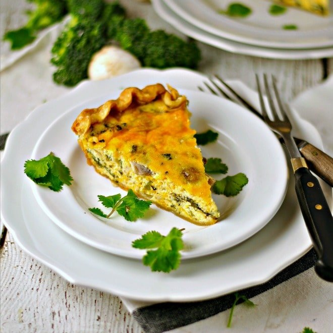 A slice of Vegetable Cheddar Quiche on a white plate with two forks