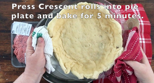 A prebaked crescent roll crust in glass pie plate