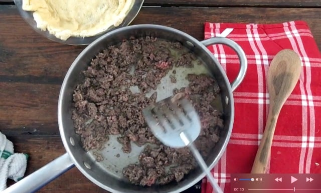 Ground beef in a frying pan with a red napkin and wooden spoon