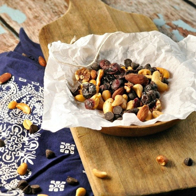 Trail mix wrapped in paper with a bandana and cutting board in background