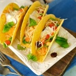 Three chicken tacos on a white plate