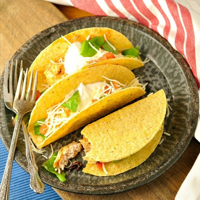Three chicken tacos on a grey plate with a red and white napkin