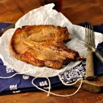 Marinated pork chops on wax paper with two forks and a blue napkin