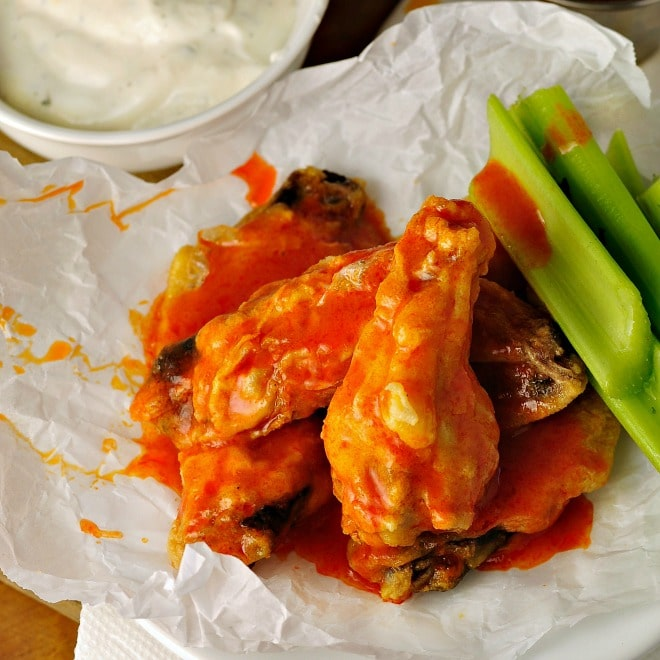 Healthier Baked Chicken Wings on wax paper with buffalo sauce