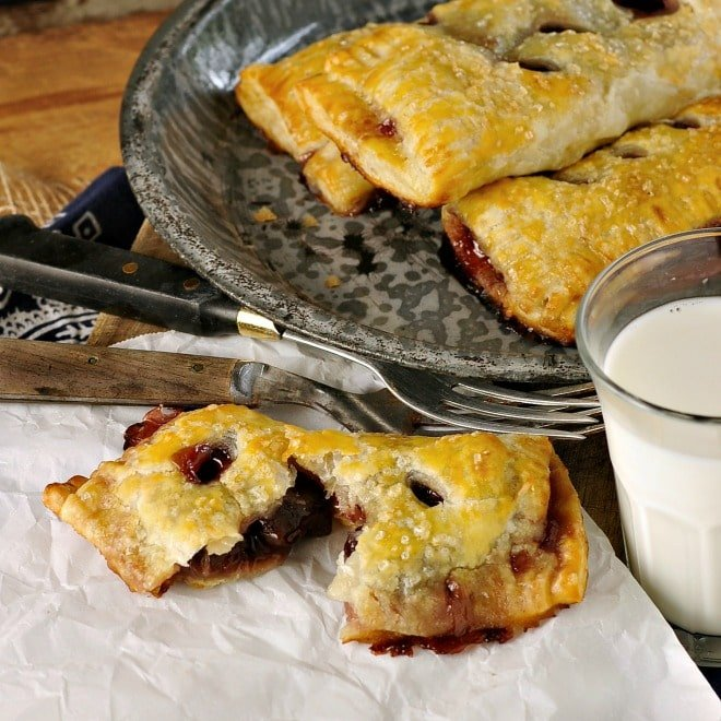 Cherry hand pies split open with a glass of milk and forks