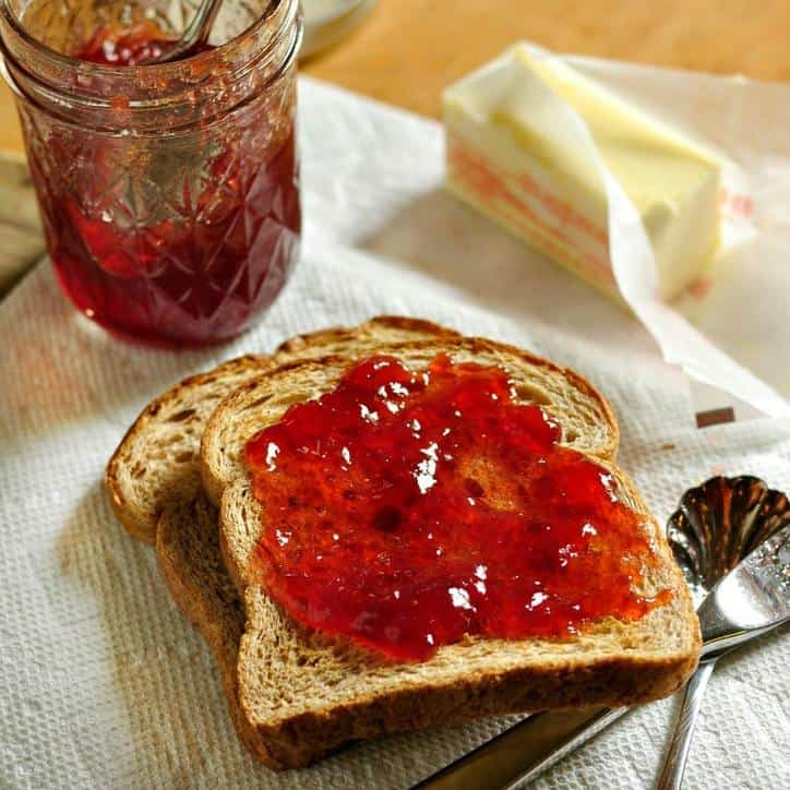 strawberry jam on toast with butter and spoon