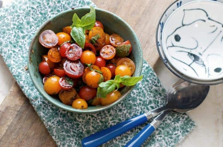 A photo from above of Summer Cherry Tomato Salad showing some blue silverware and smaller serving dishes