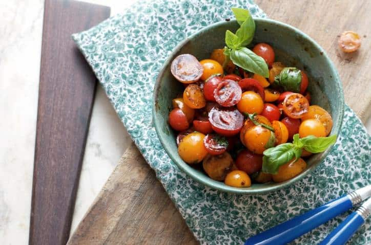A photo from above of Summer Cherry Tomato Salad showing the green placemat and one piece of silverware