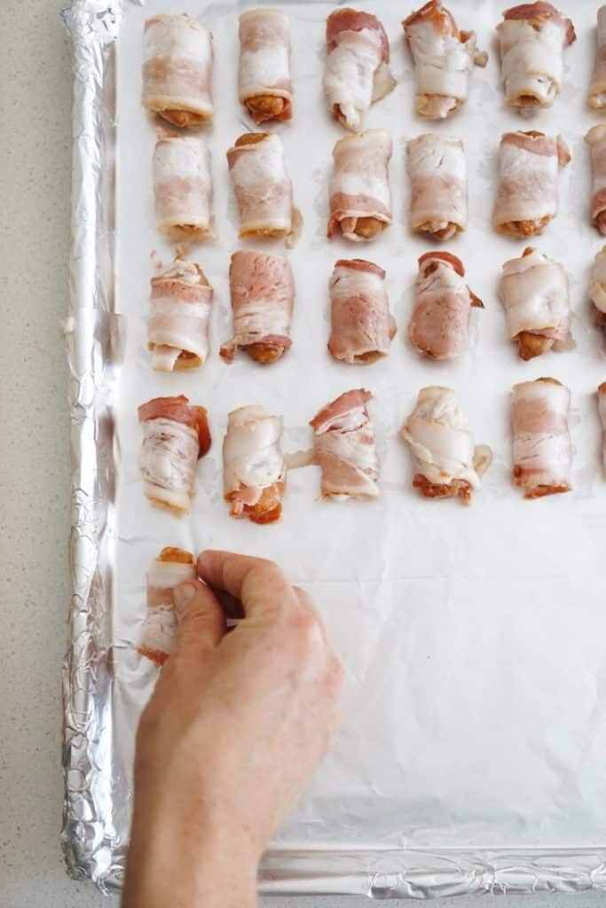 A photo of the bacon wrapped smokies on the baking sheet