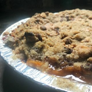 A photo of the baked pie - up close from the side Peach Pie with a Pecan Brown Sugar Crumble