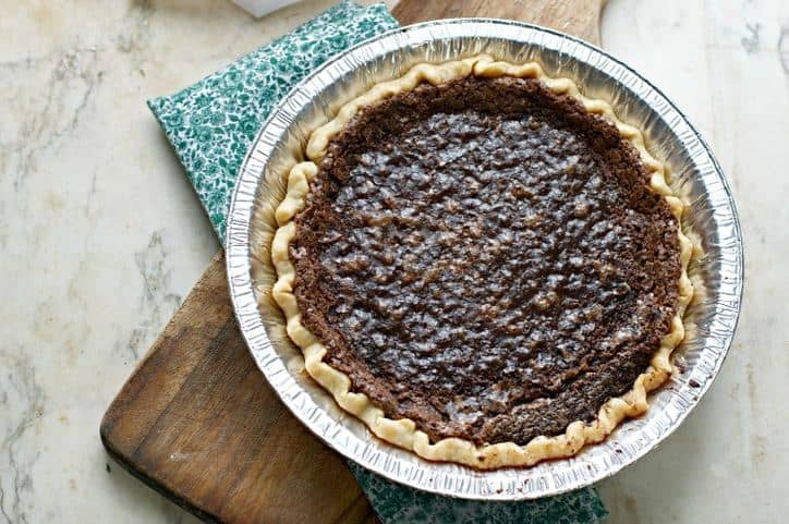 A different overhead shot of the CHOCOLATE CHESS PIE with a cutting board and prairie print napkin beneath