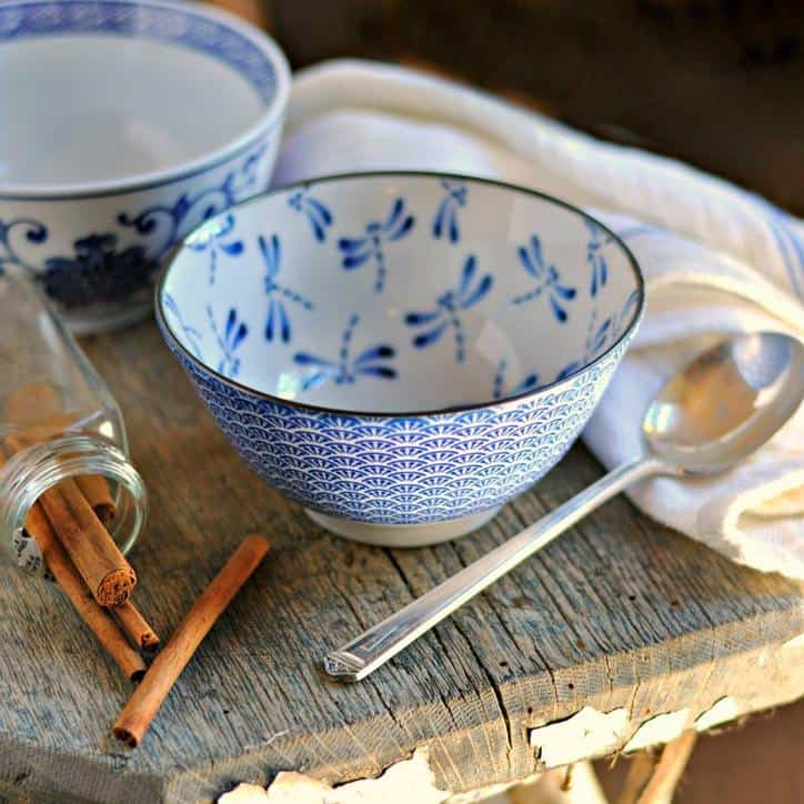 An empty blue bowl with a dragon fly print, cinnamon sticks, a spoon and a kitchen towel