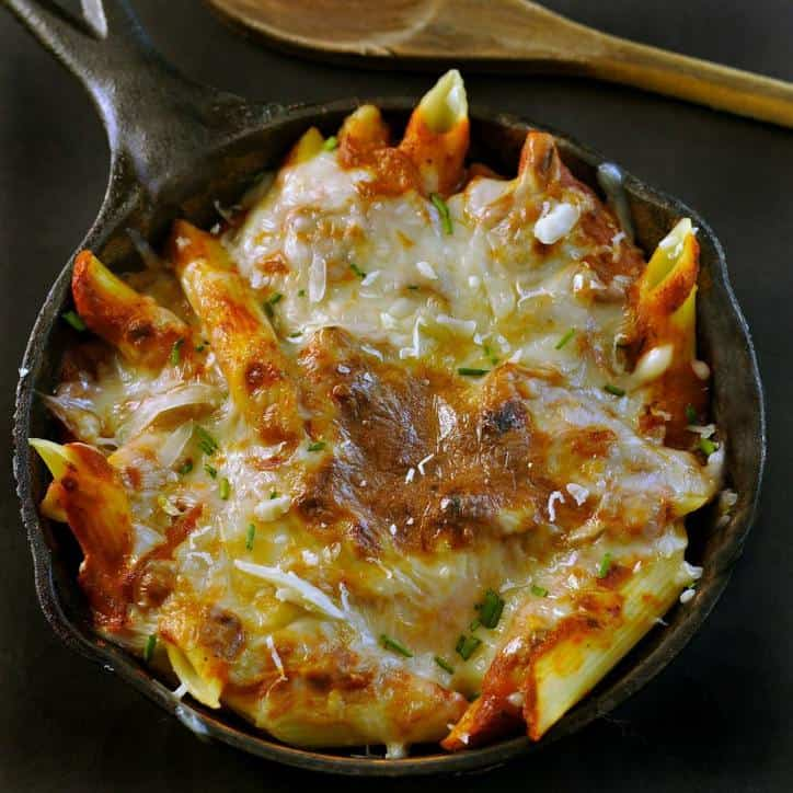 Black Cast iron skillet and wooden spoon with cheese and sauce covered pasta in the skillet.