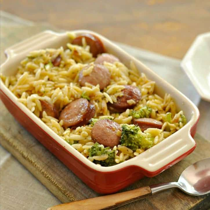 A casserole dish and a spoon of Smoked Sausage and Cheesy Orzo @loavesanddishes.net