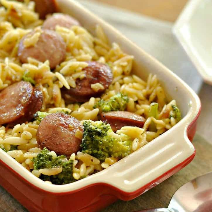 A photo of a casserole dish of Smoked Sausage and Cheesy Orzo @loavesanddishes.net